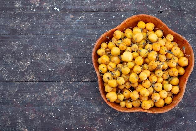 Gelbe frische kirschen der draufsicht süße milde und saftige innenplatte auf dem frischen süßkirschfoto der grauen hintergrundfrucht
