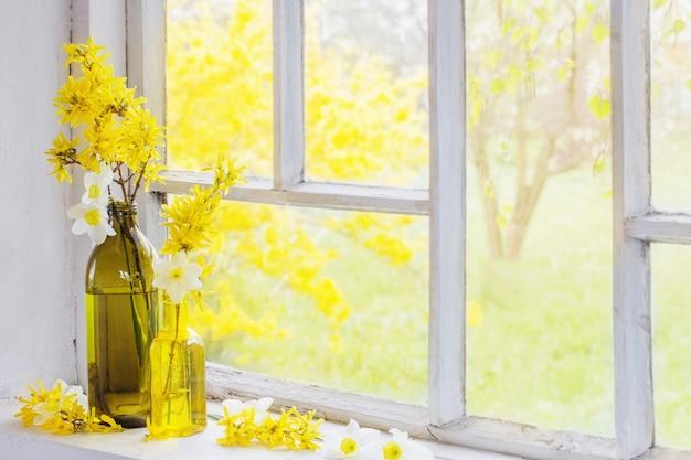Gelbe frühlingsblumen auf altem weißem fensterbrett