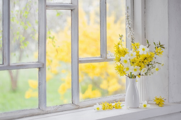 Gelbe frühlingsblumen auf fensterbank