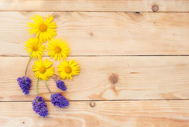 Gelbe frühlingsblumen werden auf einem hölzernen hintergrund ausgelegt. draufsicht.