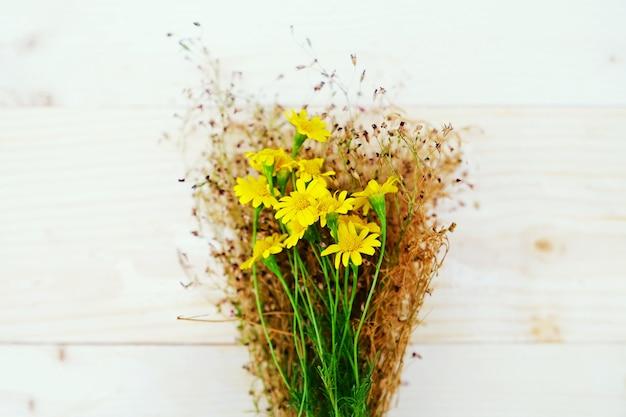 Gelbe gänseblümchen und baby atem auf dem tisch holz