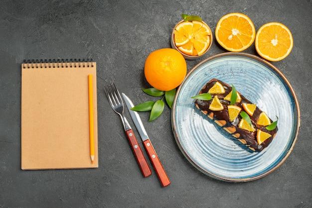 Gelbe ganze und geschnittene zitronen leckere kuchen mit gabel und messer neben notizbuch auf dunklem tisch
