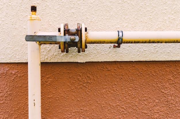 Gelbe gasleitung mit kran verläuft entlang der fassade eines neuen mehrstöckigen gebäudes.