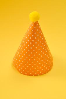 Gelbe geburtstagsmütze auf gelber fläche