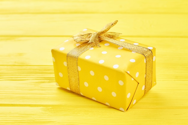 Gelbe geschenkbox auf gelbem hintergrund.