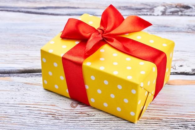 Gelbe geschenkbox mit rotem band.