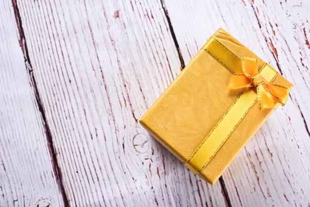 Gelbe geschenkbox mit schleifenband auf dem weißen holztisch, geburtstag, weihnachtstagskonzept. geschenkkonzept annehmen