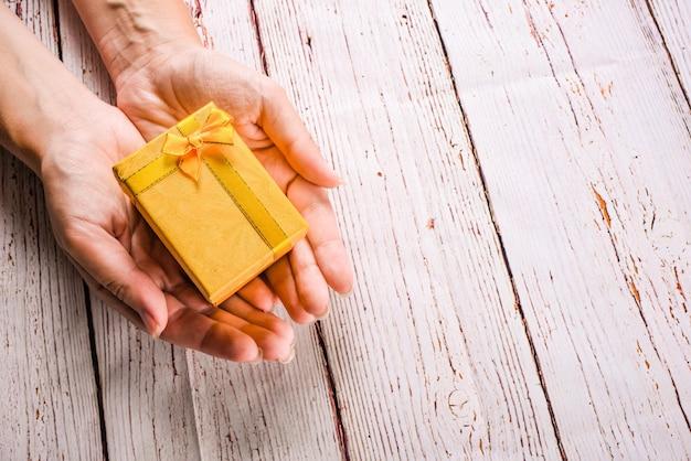 Gelbe geschenkbox mit schleifenband in frauenhänden auf dem weißen hölzernen raum