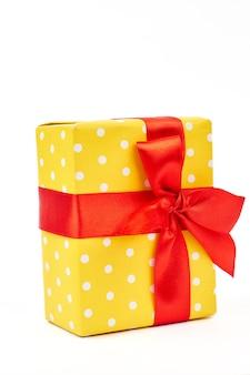 Gelbe geschenkbox mit tupfenmuster.