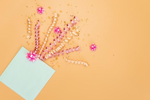 Gelbe geschenkbox mit verschiedenen partykonfettis, ausläufern, krachmachern und dekoration auf einem orangefarbenen hintergrund.