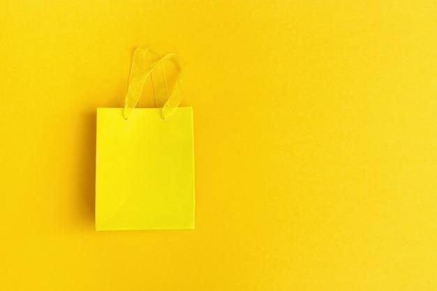 Gelbe geschenktüte auf gelbem papierhintergrund