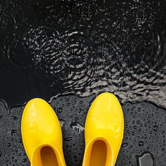 Gelbe glänzende gummistiefel stehen im regen auf schwarz
