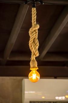 Gelbe glühbirne die kugel hängt mit einem seil.