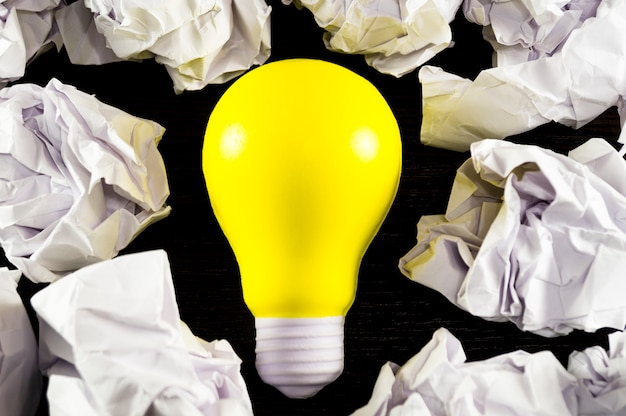Gelbe glühlampe als symbol der idee auf einem dunklen hintergrund