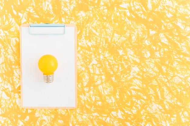 Gelbe glühlampe auf weißbuch über klemmbrett gegen gelben hintergrund