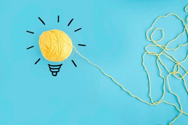 Gelbe glühlampe des belichteten garns auf blauem hintergrund