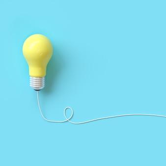 Gelbe glühlampe mit draht auf blauem hintergrund für copyspace.