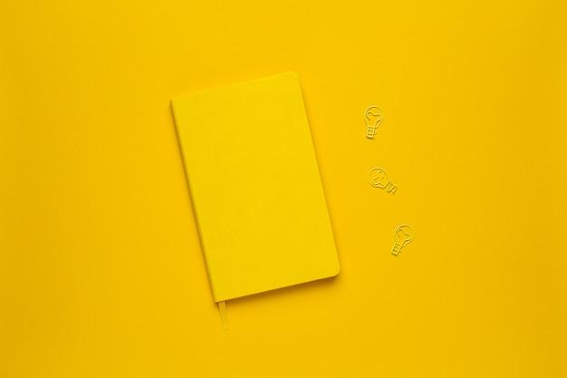 Gelbe glühlampeidee des notizbuches und der papierklammer auf gelb