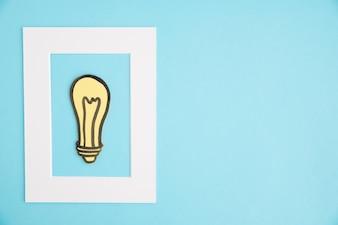 Gelbe Glühlampe innerhalb des weißen Rahmens auf blauem Hintergrund