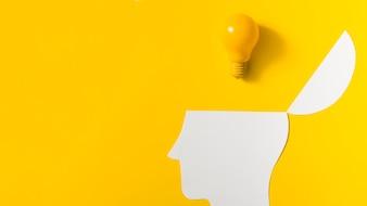Gelbe Glühlampe über dem offenen Papier schnitt Kopf gegen farbigen Hintergrund aus
