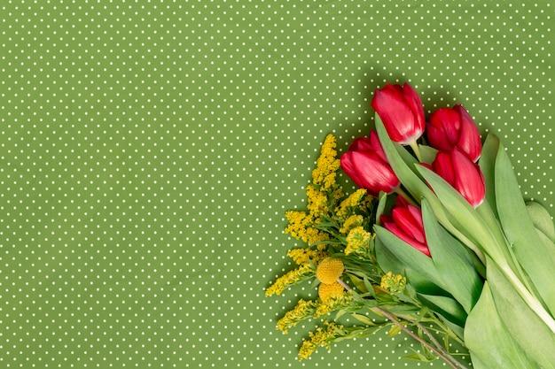 Gelbe goldrute und rote tulpe blüht auf ecke des grünen tupfenhintergrundes