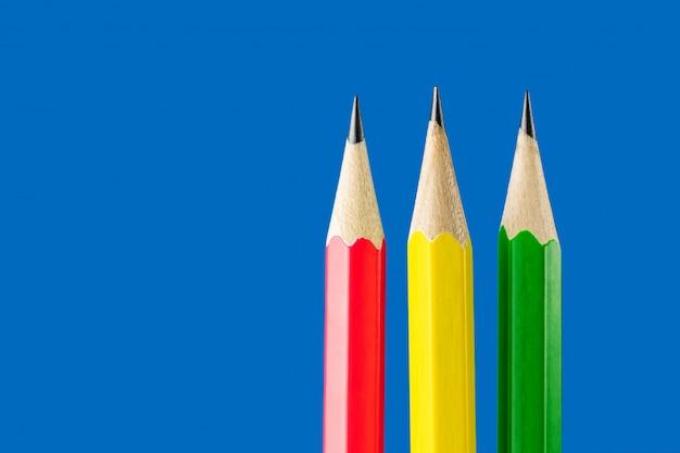 Gelbe, grüne und rote bleistiftnahaufnahme auf einem blauen hintergrund.