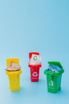 Gelbe, grüne und rote papierkörbe mit recycling-symbol