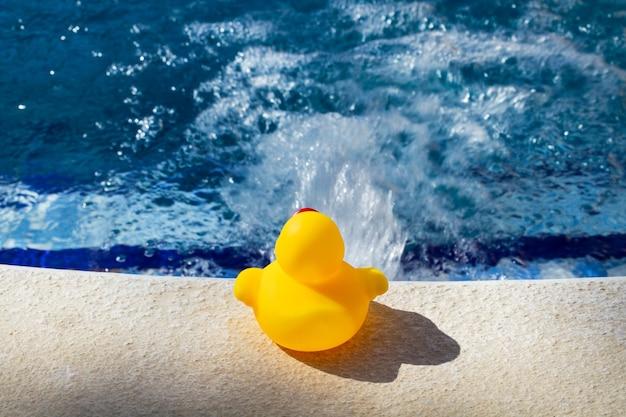 Gelbe gummiente am rand eines schwimmbeckens