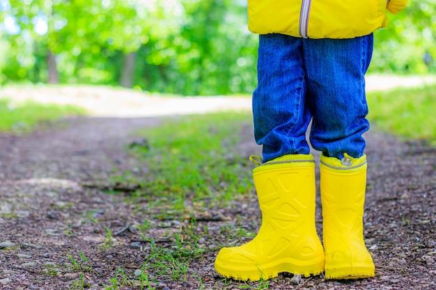 Gelbe gummistiefel an den füßen des kindes im park