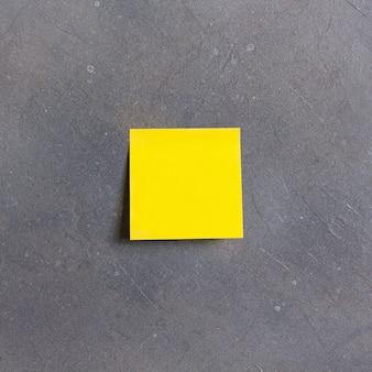Gelbe haftnotiz auf grauem hintergrund. hochwertiges foto