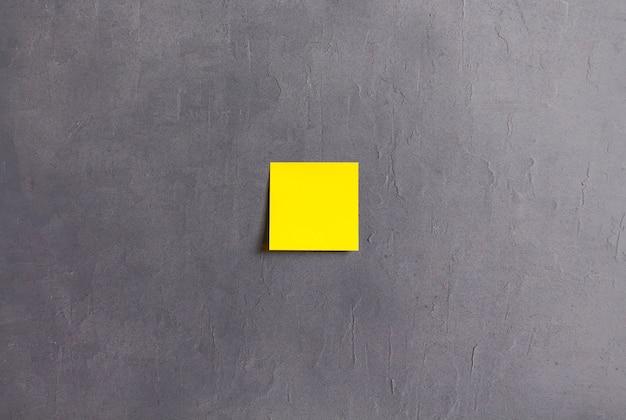 Gelbe haftnotiz auf grauem zementhintergrund. hochwertiges foto