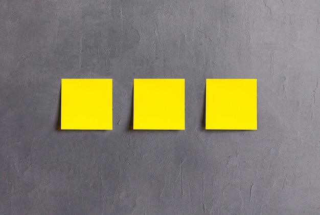 Gelbe haftnotizen auf grauem zementhintergrund.