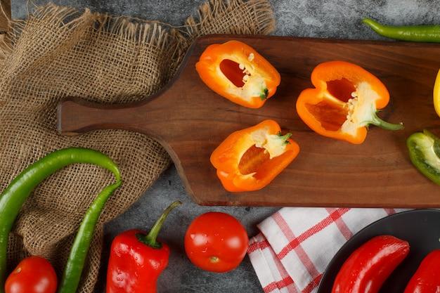Gelbe halb geschnittene paprika auf einem holzbrett. draufsicht.