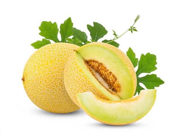 Gelbe halbe melone melone mit blättern auf weißem tisch.