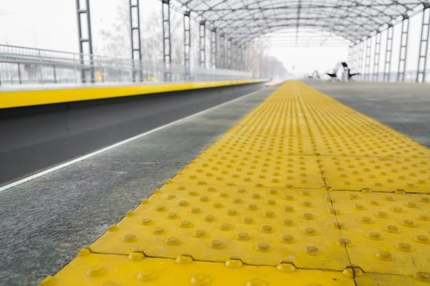 Gelbe haltelinie für blinde am bahnhof in der perspektive