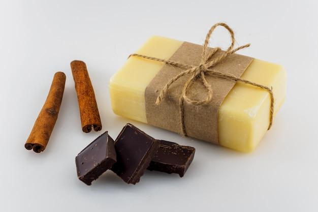 Gelbe handgemachte seife mit schokolade und zimt auf weißem hintergrund.