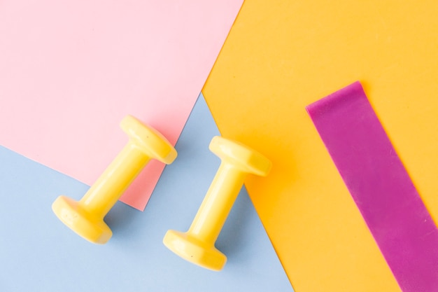 Gelbe hantelfarbe auf rosa, blauer und gelber matte. design eines sportplakats oder banners in modischen farben von 2021