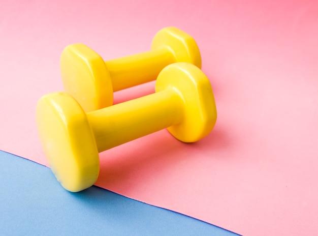 Gelbe hantelfarbe auf rosa blauer und gelber matte design eines sportplakats oder -banners