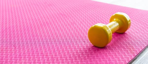 Gelbe hanteln auf einem leeren rosa gummiboden auf holzbodenhintergrund, draufsicht mit kopienraumgesundheits- und übungskonzept