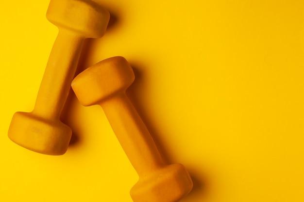 Gelbe hanteln liegen auf gelbem grund, das konzept von sommer, training, sport
