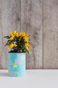 Gelbe heiße paprikapfeffer in gemaltem behälter auf dem tisch gegen hölzerne wand
