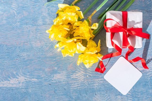 Gelbe helle narzissen, weiße geschenkbox mit rotem band und leere weiße karte auf blauem hölzernem hintergrund.
