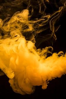 Gelbe helle rauchwolken breiteten sich weit gegen den hintergrund des dunklen schwarzen aus