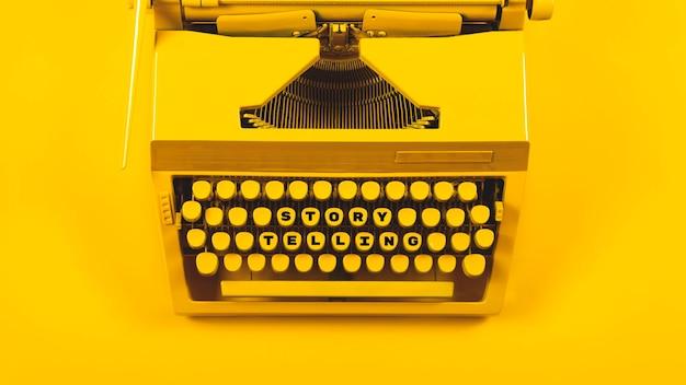 Gelbe helle schreibmaschine als symbol für schreiben, neue ideen, kreativität und geschichtenerzählen
