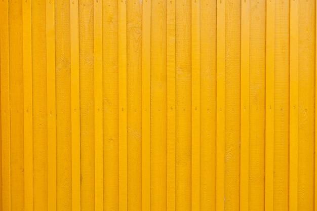 Gelbe hölzerne tabby strukturierte wand hintergrund. wand des holzhauses ist gelb gestrichen. gemalter vertikaler gelber hölzerner wiedergabewandhintergrund. wandgestaltung