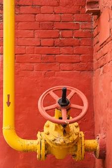 Gelbe industriegasleitung mit winkelstück und absperrventil mit drehgriff