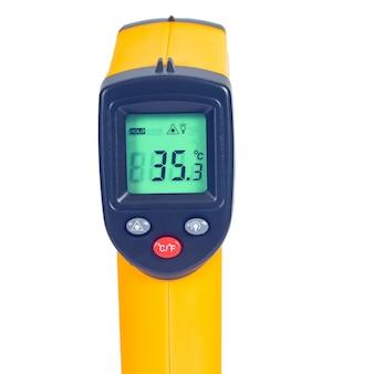 Gelbe infrarot-thermometerpistole zum messen der temperatur auf weiß.