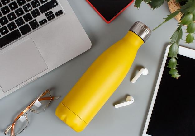 Gelbe isolierflasche auf grauem schreibtisch, umgeben von modernen geräten und pflanzen in einer vase-draufsicht