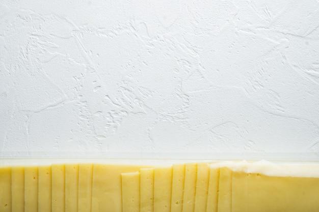 Gelbe käsescheiben in versiegelter packung auf weißem tisch