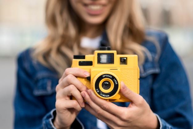 Gelbe kamera der vorderansicht und unscharfe frau